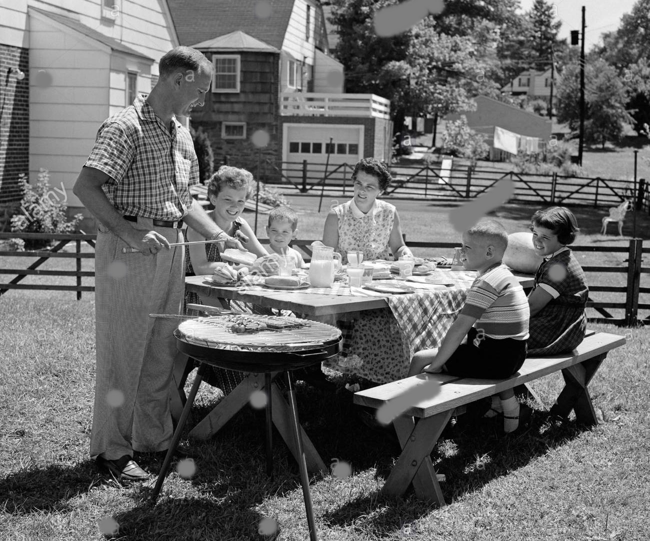 1950s-family-in-backyard-cooking-hot-dogs-sitting-at-picnic-table-AAKTPY